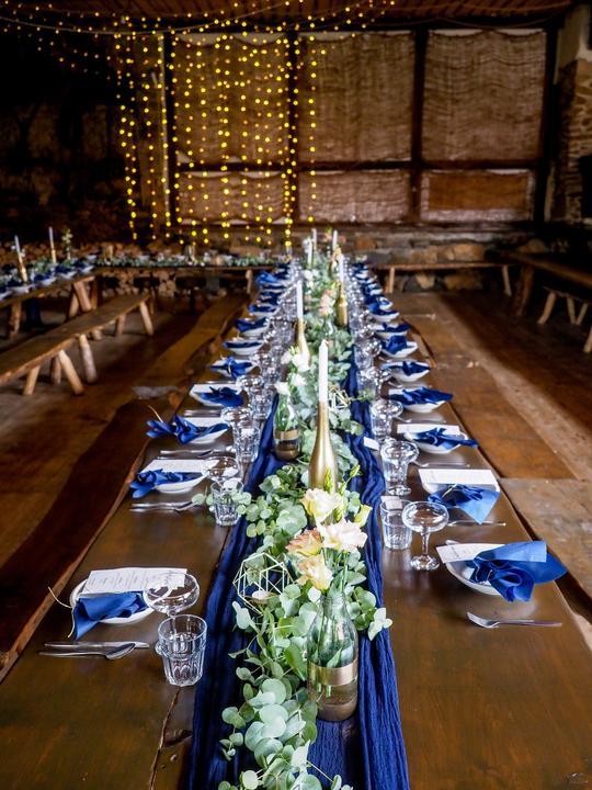 tmavě modrá a zlatá svatební výzdoba ve stodole
