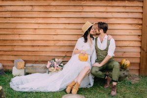 novomanželé oblečené v boho stylu sedí u dřevěné stěny s dýní